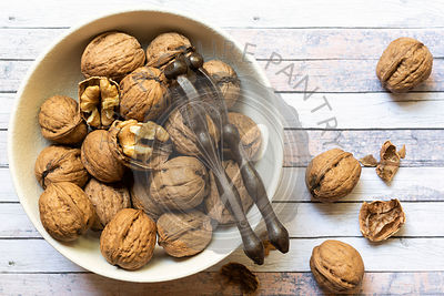 Cracked and whole walnuts in a bowl.