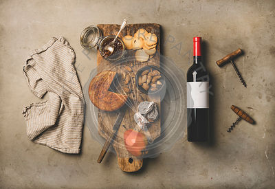 Wine bottle, vintage corkscrews, linen towel and appetizers board