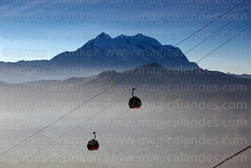 Yellow Line cable car gondolas and Mt Illimani shortly after sunrise, La Paz, Bolivia