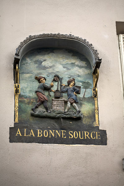 France - Paris - A shop sign from 1592 now on a wall above a shop front in the market on the Rue Mouffetard.