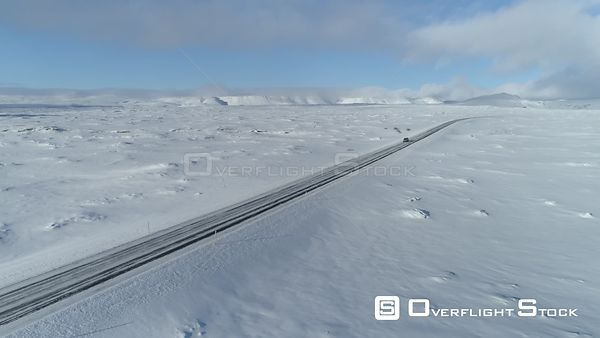 Lone Car Driving Through Snowy Winter Landscape Iceland Aerial Day