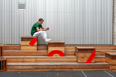A Man Sits On Wooden Benches Whilst Using His Mobile Telephone
