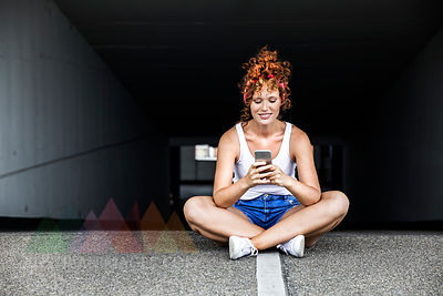 Redheaded woman sitting on parking level holding cell phone