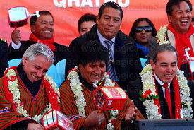 Bolivian president Evo Morales (centre) and vice president Alvaro Garcia Linera left) hold rattles in the form of cable car c...