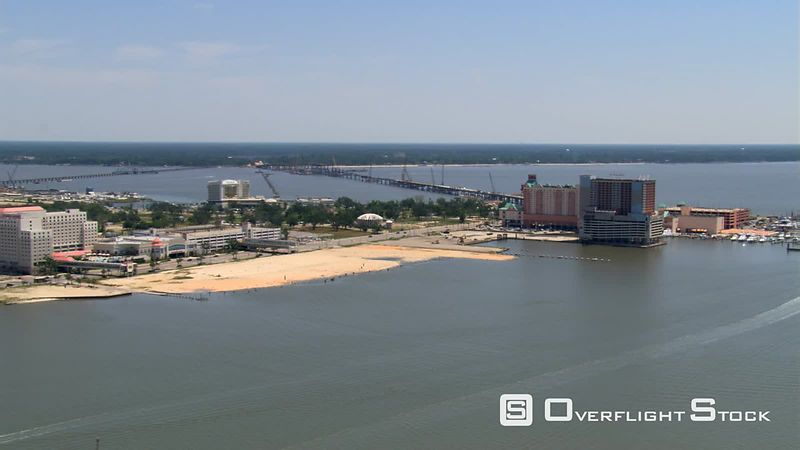 Flight along waterfront past Biloxi, Mississippi, with causeways in background.