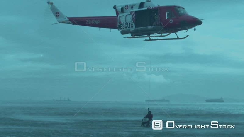 Aerial slow motion shot of a rescue helicopter airlifting two men out of the sea Cape Town Western Cape South Africa