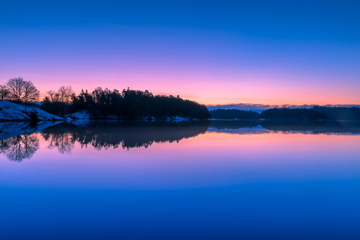 Snowy forest reflected in serene lake at blue hour