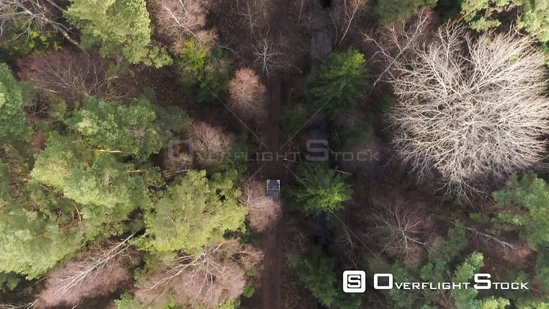 Aerial topdown drone shot of a 4x4 off road vehicle driving on a forest road Latvia