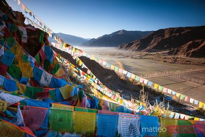 Tibetan prayer flags and valley at sunrise, Tibet