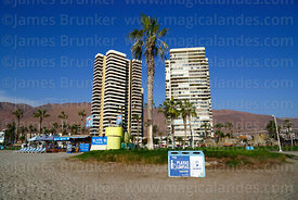 High rise apartment blocks and clean beaches campaign rubbish bins on Playa Cavancha, Iquique, Chile