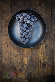 Bowl of deep frozen blue grapes on wood