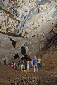 A guide talking to a tour group in a cave filled with stalictites.