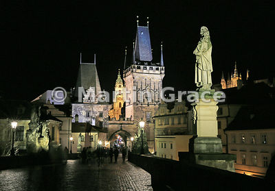 West end of Charles Bridge illuminated at night, Prague, Czech Republic