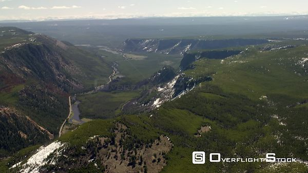 The Madison River winds through a canyon and lush green valley in Yellowstone National Park
