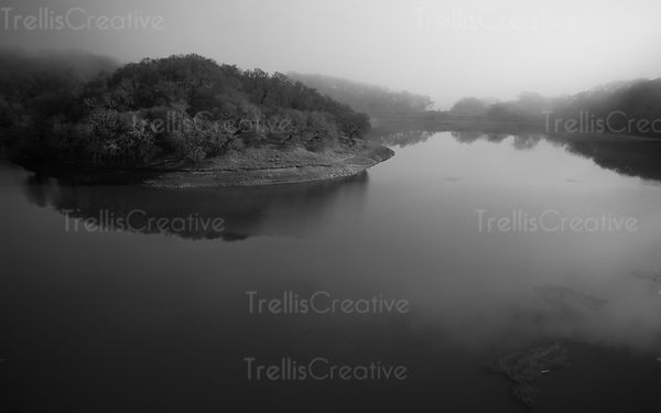 Aerial view of a calm river curving around a mist covered forest.