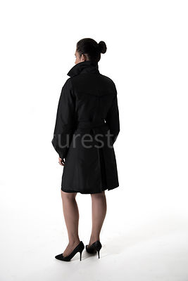 A mystery woman in a black mac, standing and looking away – shot from eye level.