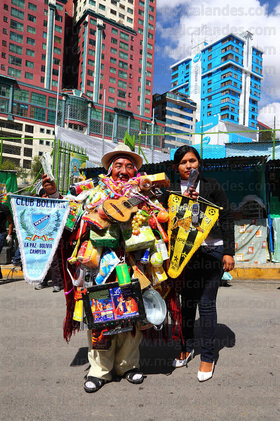 A girl poses for photos with Ricardo Paco (the official ekeko) at the Alasitas festival, La Paz, Bolivia