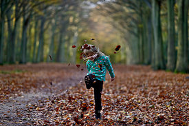 Young girl kicking fallen leaves in woodland Norfolk UK