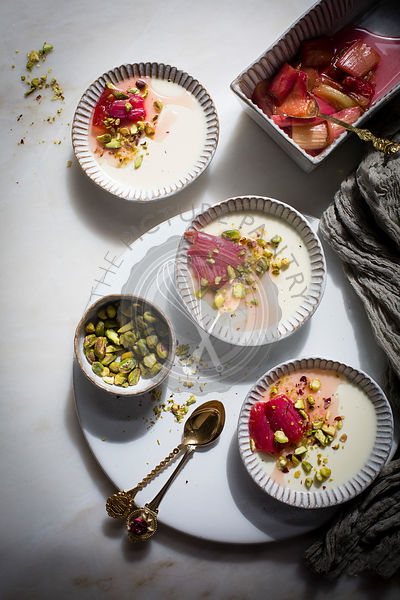 Classic vanilla pannacotta topped with roasted rhubarb and chopped pistachios in a ceramic tart pan on a marble table on top ...