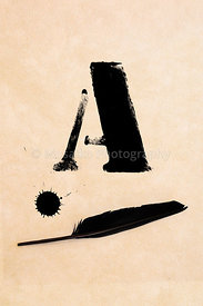 Old black, frayed grunge A - letter, inkblot and black feather on brown paper