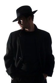 A Figurestock image of a mystery man in a black coat and Fedora hat, in silhouette – shot from eye level.