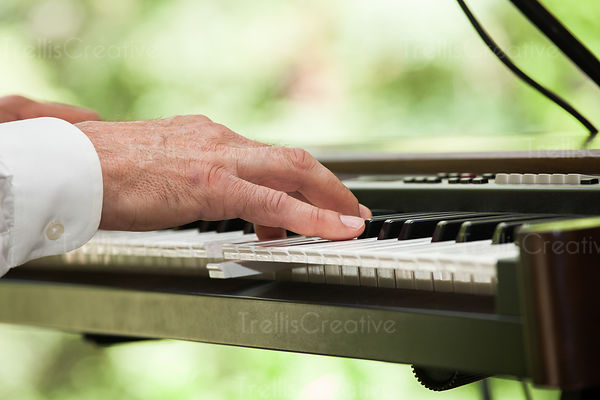 Close up photo of a man playing keyboard