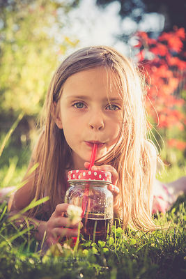 Portrait of little girl lying on a meadow in the garden drinking juice