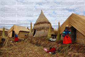 Aymara lady goes about daily life on Uros floating reed islands , Lake Titicaca , Peru