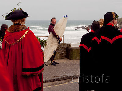 a surfer watches the St Ives Feast pageantry go by