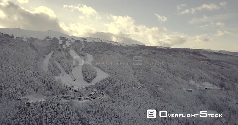 Aerial, beautiful trees under the snow and the view on the snowy mountains with ski tracks