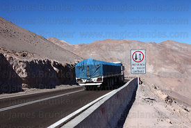 Truck approaching Give Way to Oncoming Traffic sign before hairpin bend on Ruta / Highway 11, Region XV , Chile