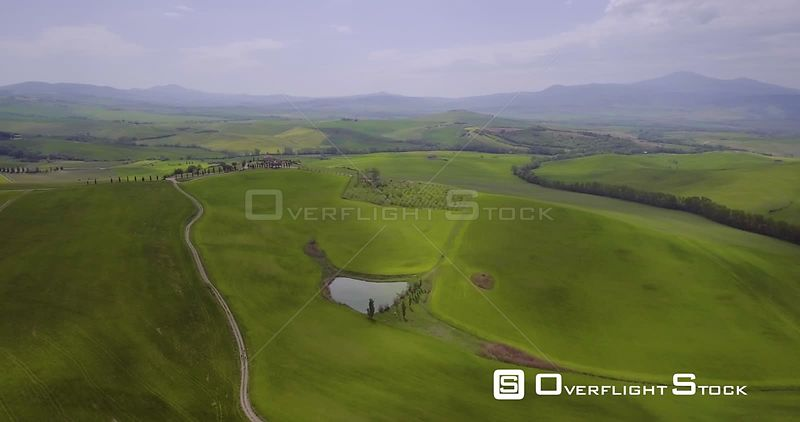 Aerial, beautiful green hills and fields and cypresses landscape in Tuscany, Italy