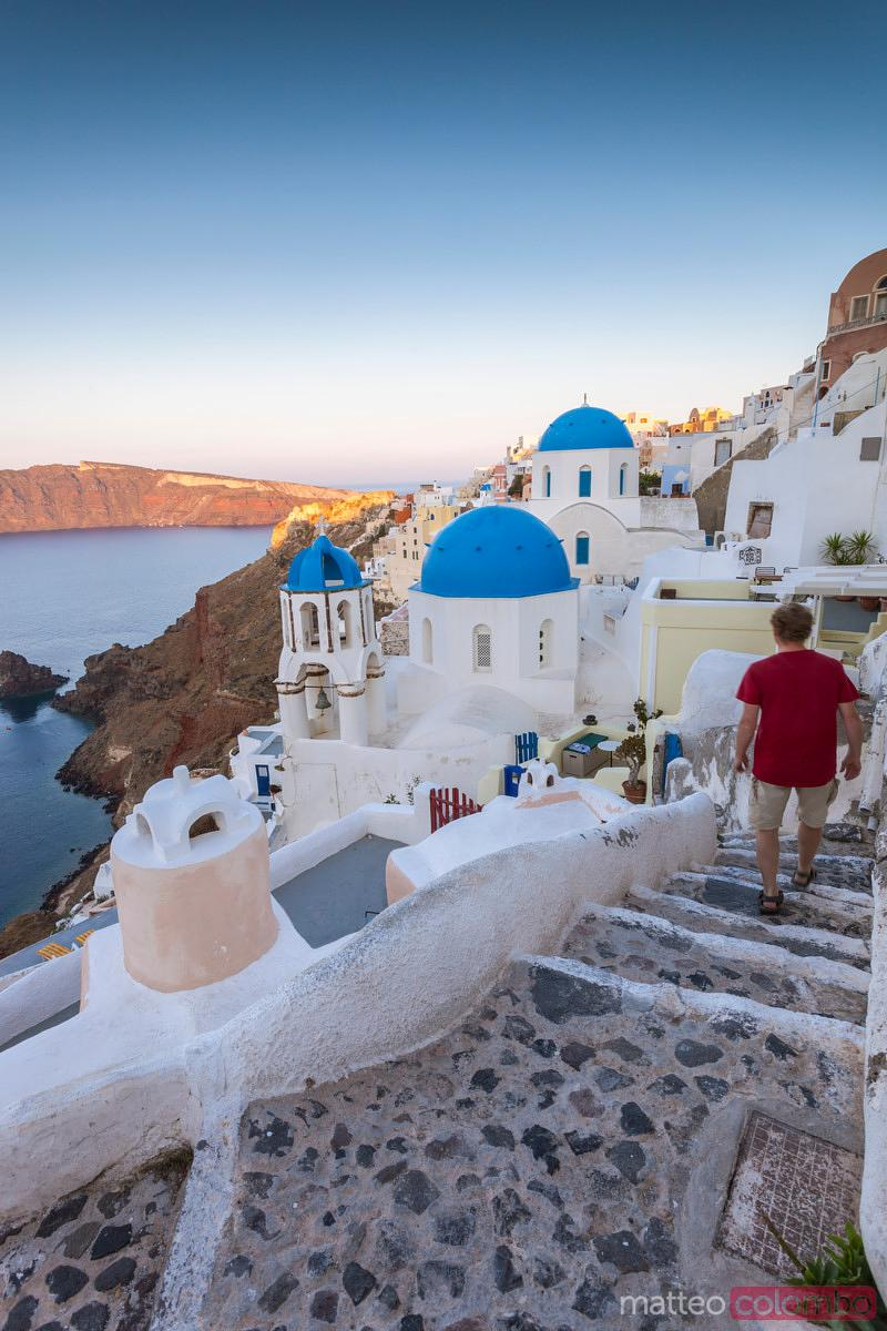 Lonely man in the village of Oia at sunrise, Santorini, Greece