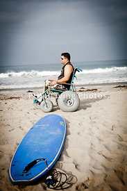 Man in a beach wheelchair on an ocean beach