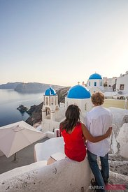 Tourist couple admiring the village of Oia, Santorini, Greece