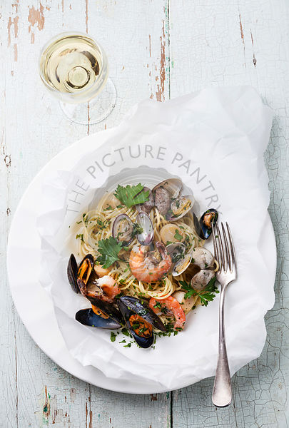 Seafood pasta - Spaghetti with clams, prawns, sea scallops on white plate
