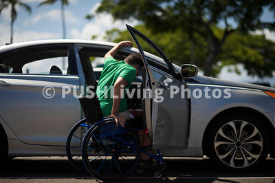 Young man in a wheelchair getting into his car