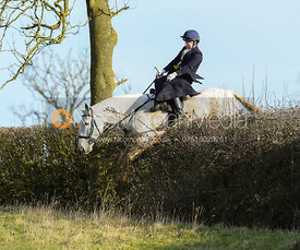 Chloe Edgar jumping a hedge near Ladywood - The Cottesmore at Priory Farm