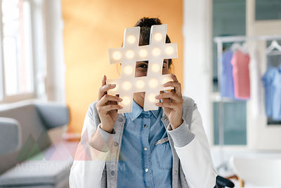 Young woman hiding behind hashtag sign in studio