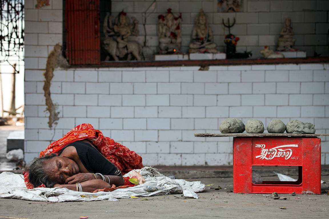 A woman selling balls of mud from the Hooghly River sleeps near Sovabazar Ghat, Kolkata, India. Sleeping in public is very co...
