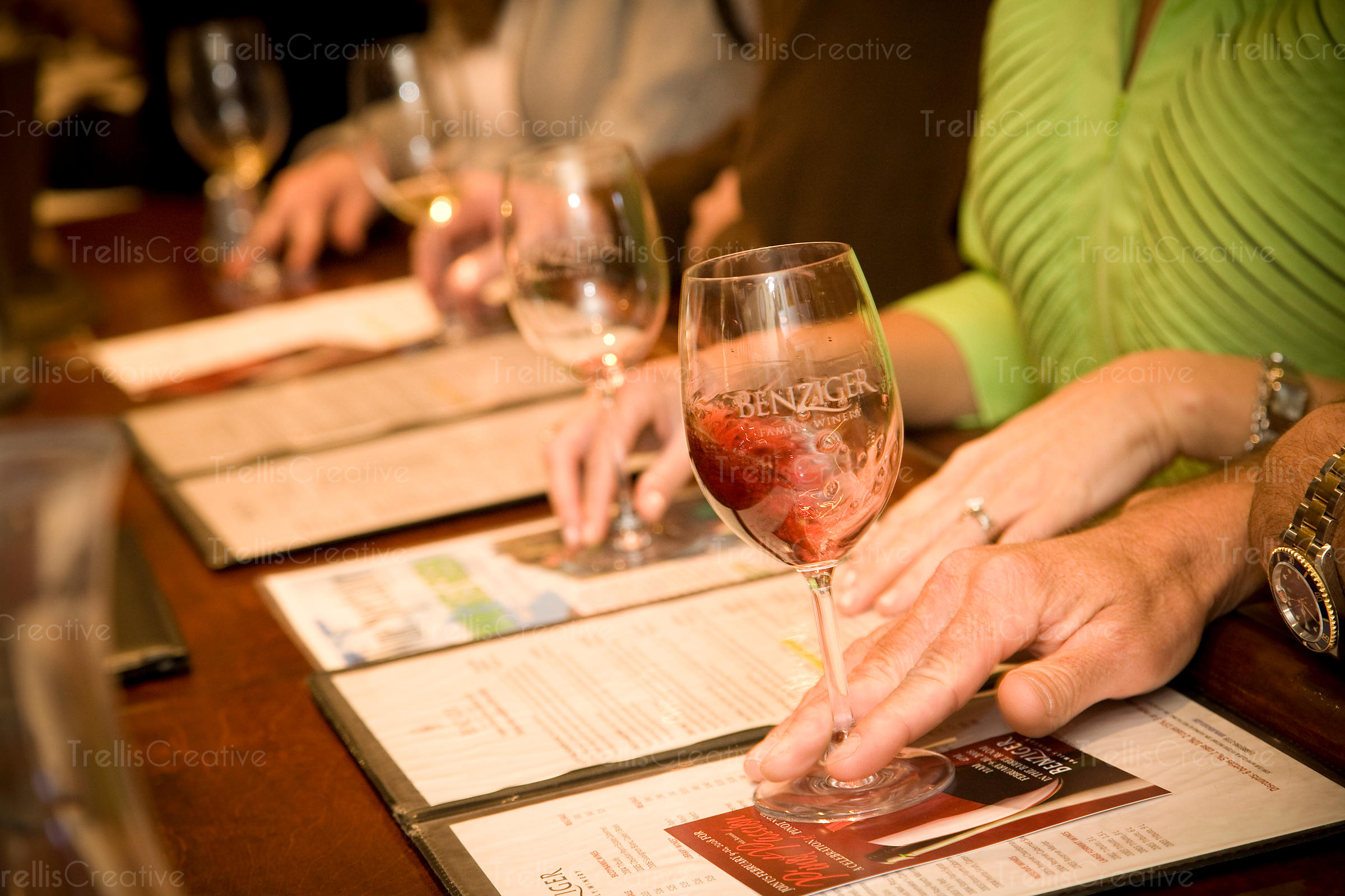 Customers swirling wine in glasses in a winery tasting room