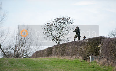A member of the Household Cavalry watches the start from the top of a hedge