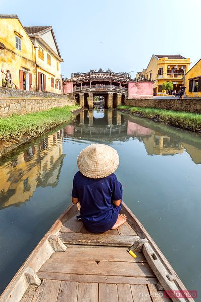 Old man looking at famous japanese bridge in Hoi An, Vietnam