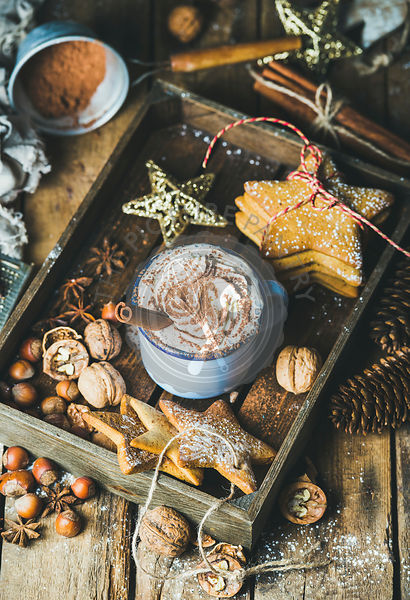 Mug of hot chocolate with whipped cream, cocoa powder, cinnamon, gingerbread cookies, nuts in wooden tray with Christmas deco...