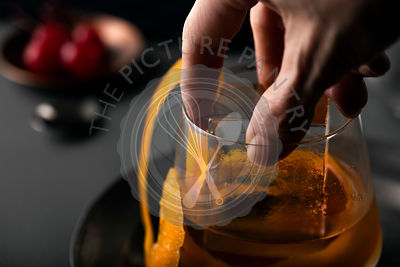 Woman placing large, clear, ice cube into glass of old fashioned cocktail.