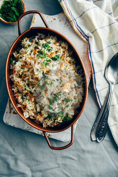 Fried rice pilaf with orzo served in a copper pan on a white board. Spoons, white napkin and a small bowl of chopped parsley ...