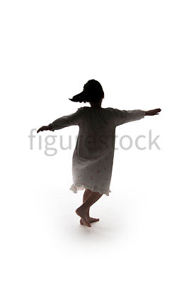 A Figurestock image of a little girl, in silhouette, dancing in a night dress – shot from eye level.
