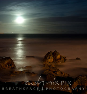 Night shot of moon rising over mountains above Gordon's Bay with path of moonlight across False Bay, orange light on rocks an...