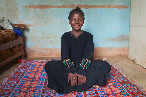 Fille assise sur une natte faisant office de lit au Burkina Fao, Afrique / Girl sitting on a mat acting as a bed in Burkina F...