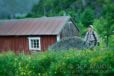 Woman walking among flowers and wooden house